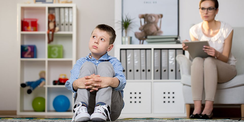 Puzzled child in foreground during consultation with behavior analyst