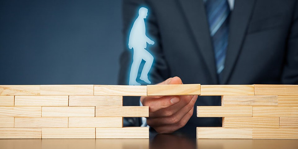 man holding wooden block to help a digital outline of another man cross a gap between two block walls