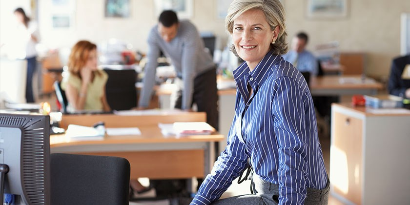 Confident, smiling woman in striped blue shirt poses for the camera in an office with personnel working in the background
