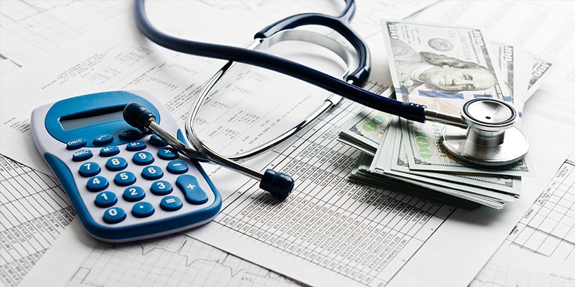 a calculator, a stethoscope, and a pile of 100 dollars bills sit atop some medical bills