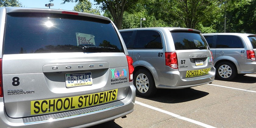 A line of Bucks IU school student minivans