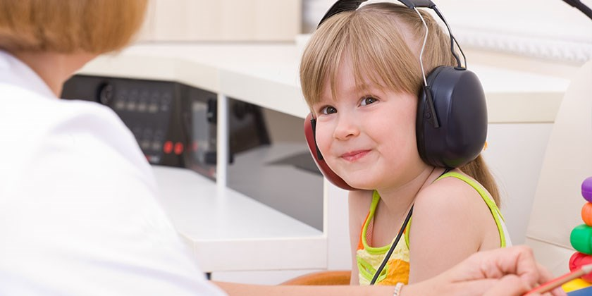 Smiling child wearing headphones being given a hearing test