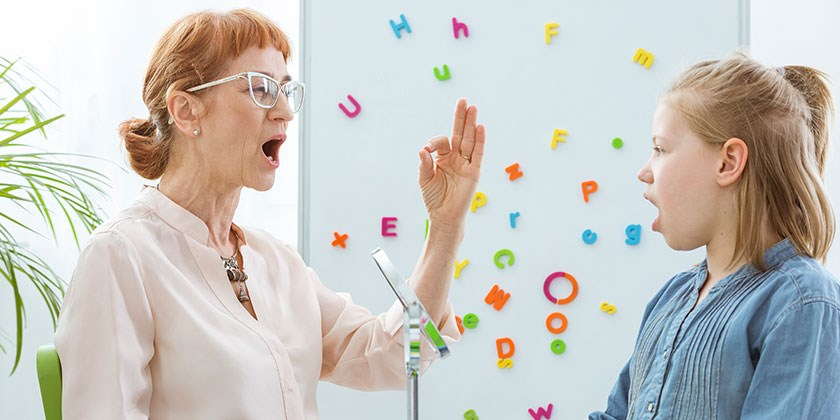 Speech therapist working with girl using hand gestures and magnetic alphabet magnets