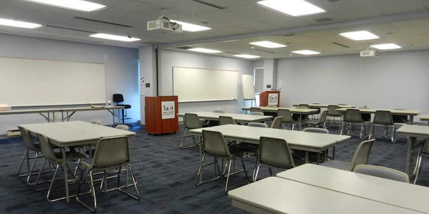 Empty meeting room with tables, chairs, projectors, and podiums ready to be used