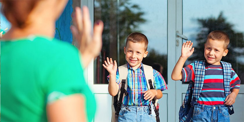 Mother waving at her children as they wave back from in front of the school's doors