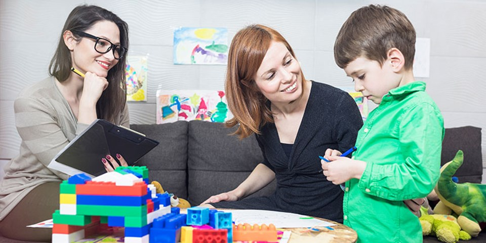 Mother and child with psychologist during play therapy session