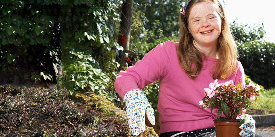 Special needs child gardening while outdoors
